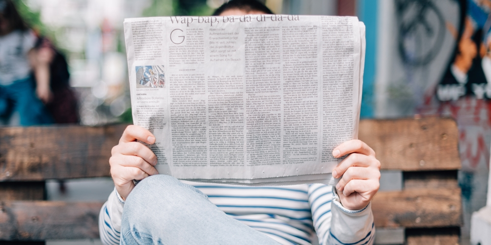 Man reading a Thinkific News newspaper on a bench
