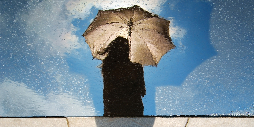 Reflection of person holding umbrella