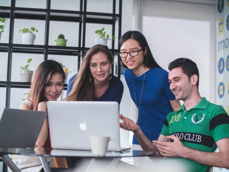 Group of people looking at a laptop to signify the power of affiliate marketing for your online course